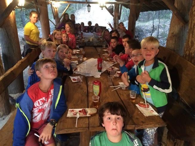 Dzieci jedzą kiełbaski na ognisku zielone szkoły góry świętokrzyskie