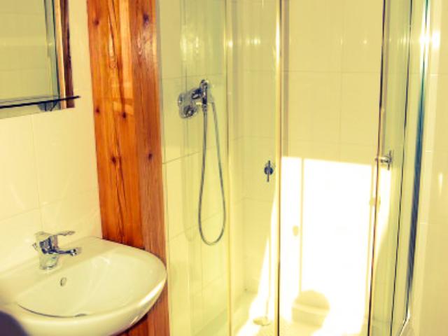 Łazienka z przyszniecem z piękną drewnianą kolumną