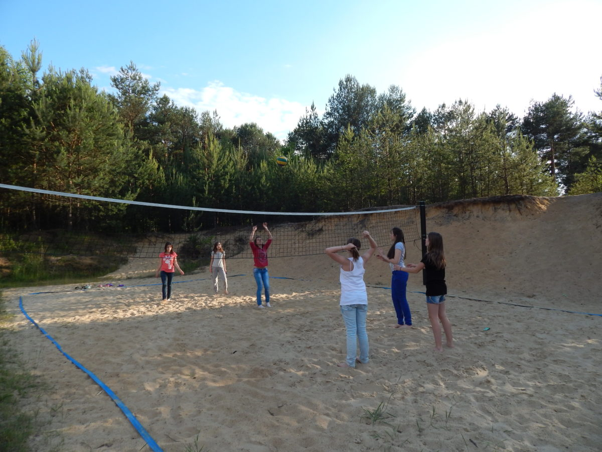 Dzieci grają w siatkówkę na terenie ośrodka